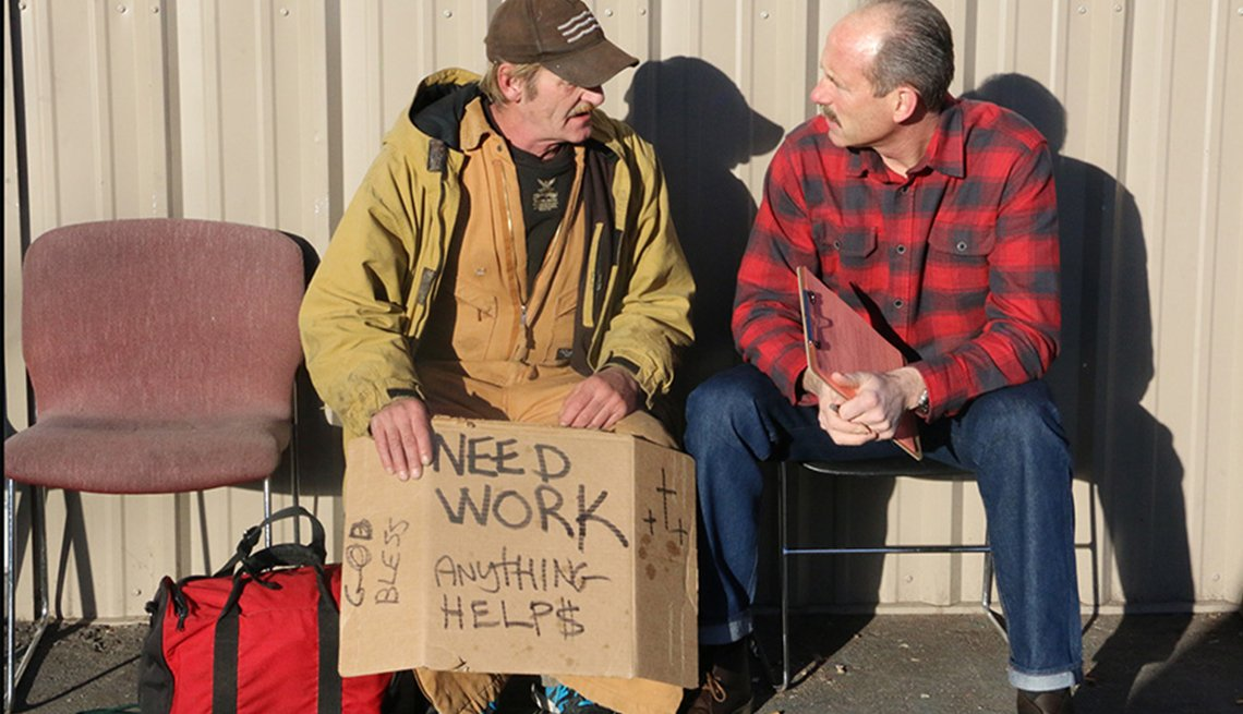 Mayor Richard Berry of Albuquerque, New Mexico, speaks with a man holding a cardboard sign that says Need Work, Anything Helps