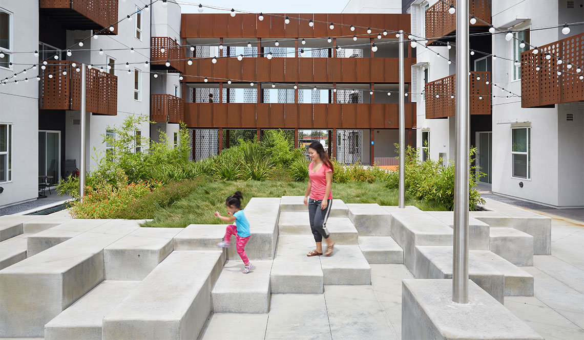 A mother and child walk through a courtyard at the Rivermark housing complex.