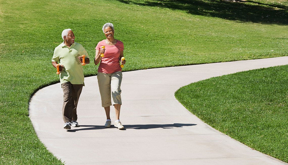 Two seniors jogging through park