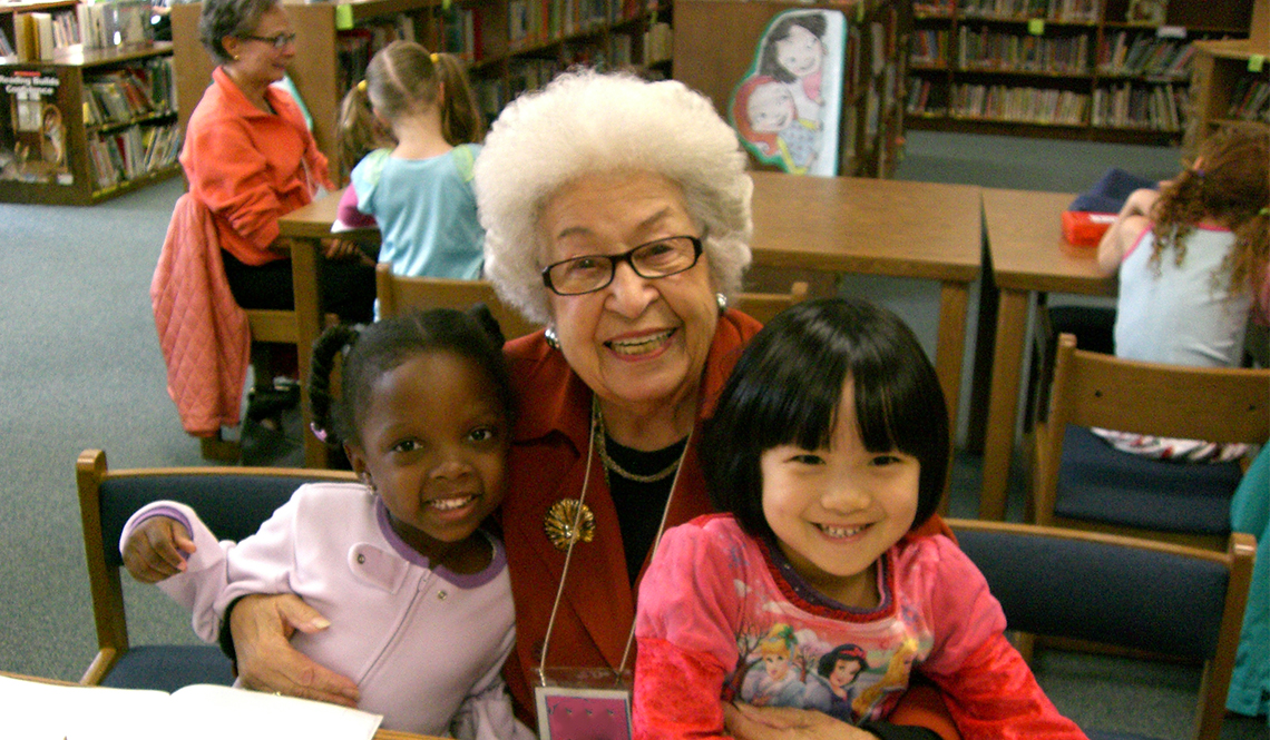 An older volunteer and two kindergartners smile during a Grandpals visit to the library