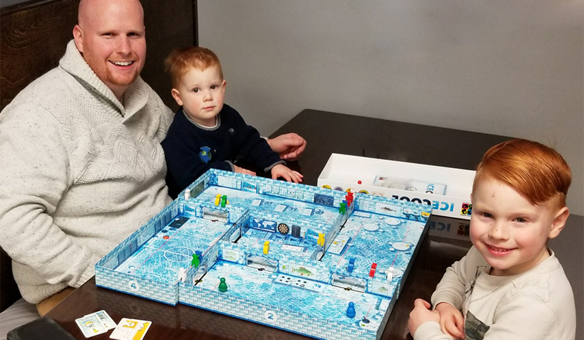 A dad and his two preschool age sons play the board game Ice Cool