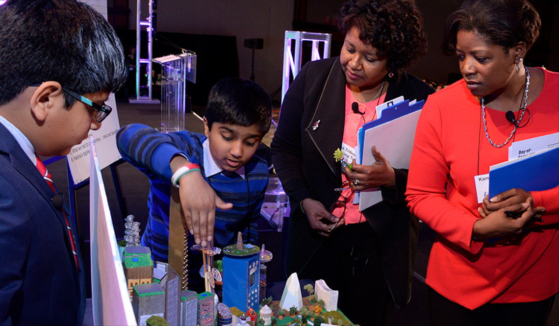 Students from the Mid-Atlantic team show AARP executive and competition judge Kamili Wilson (in red) their future city.