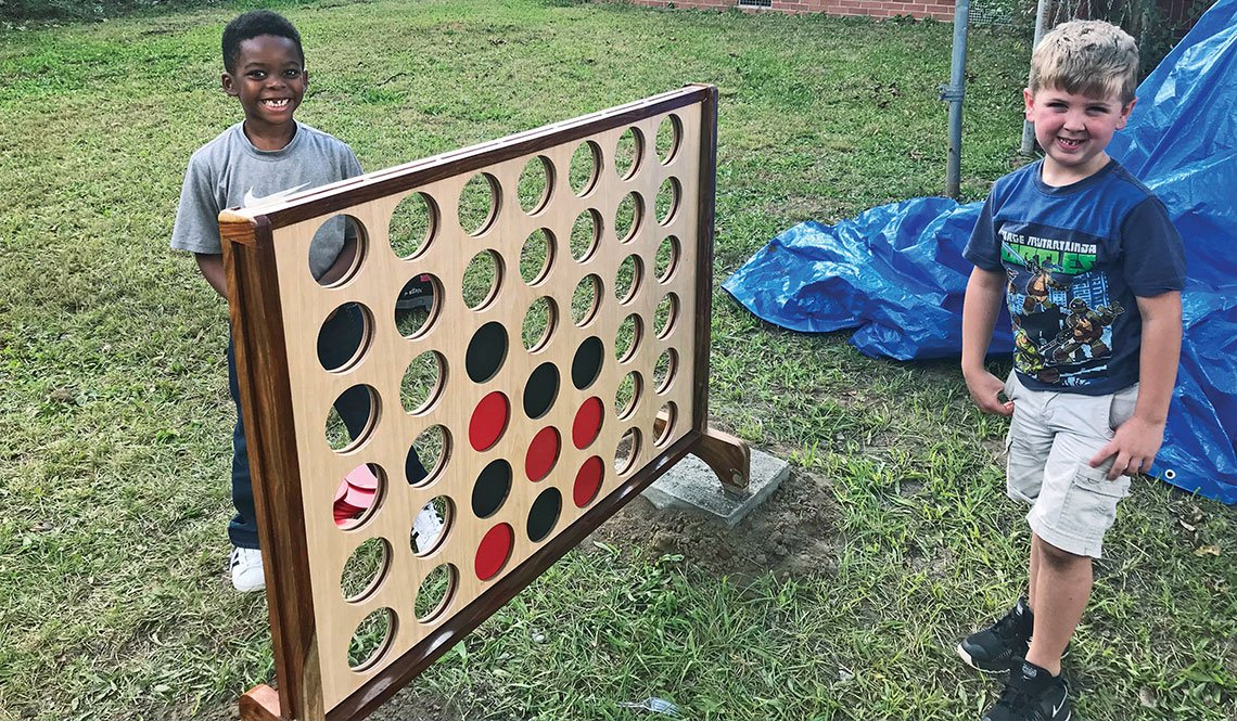 Two young boys stand next to a giant Connect4 game