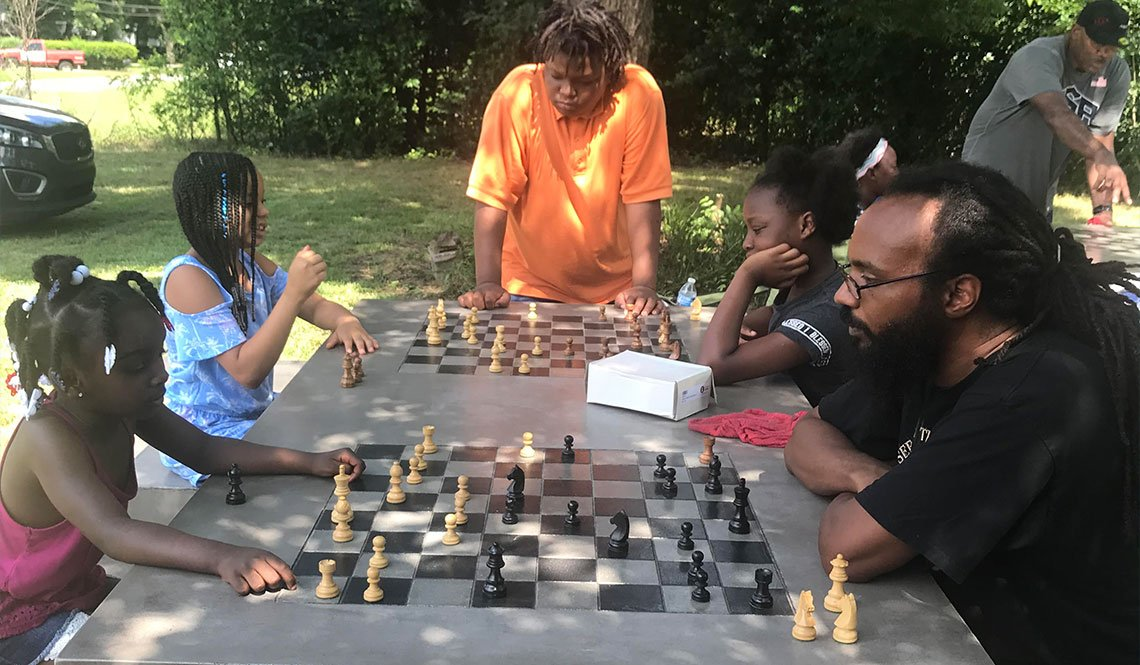Children and adults play chess outdoors in Macon, Georgia