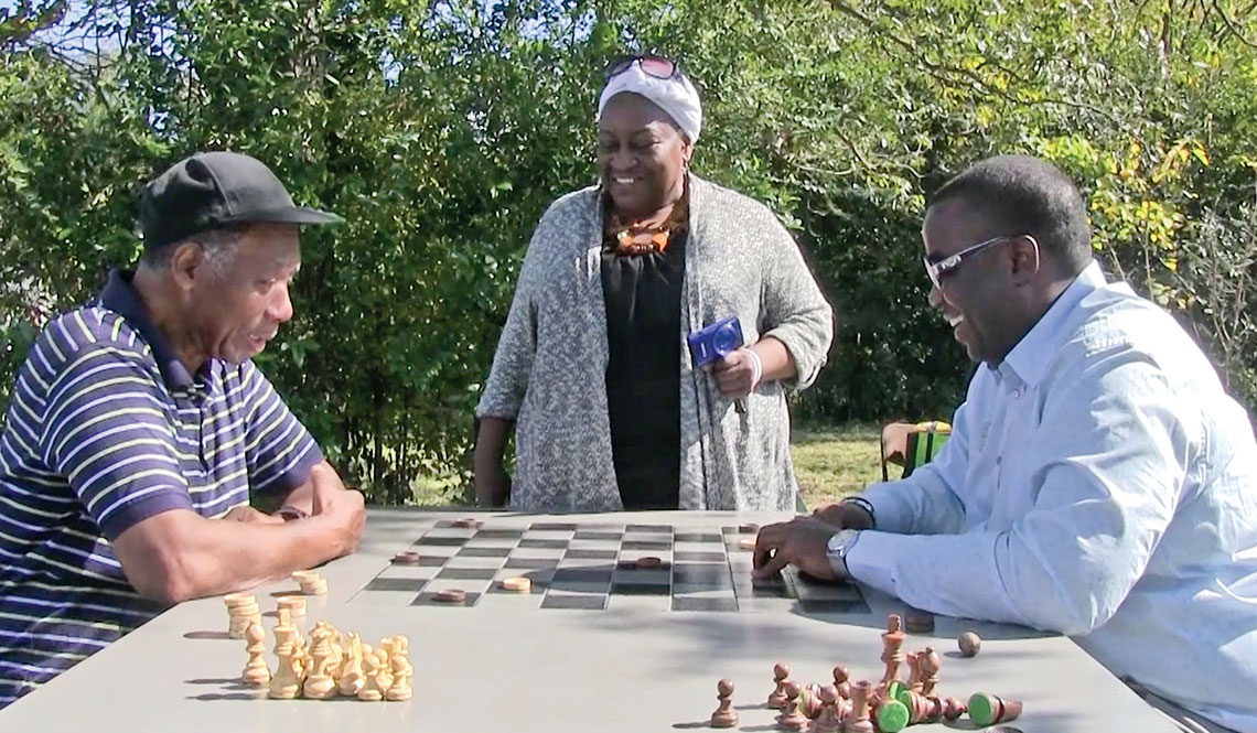 Two men play checkers on an outdoor game table in Macon, Georgia