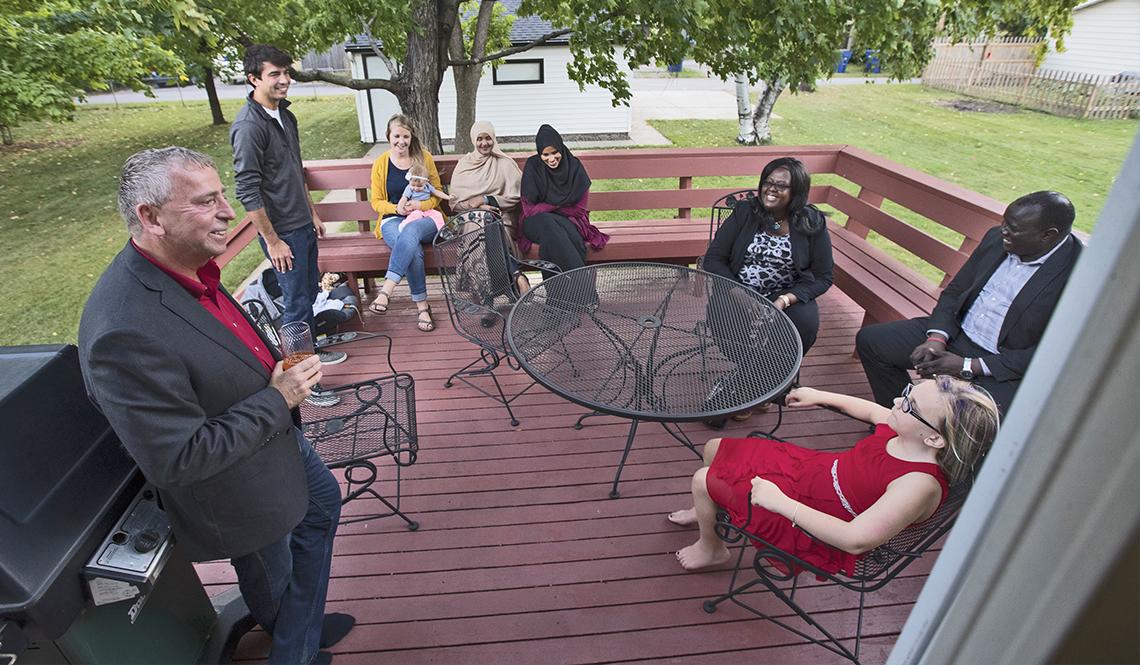 Mayor Dave Kleis of St. Cloud, Minnesota, speaks with dinner guests on his backyard deck