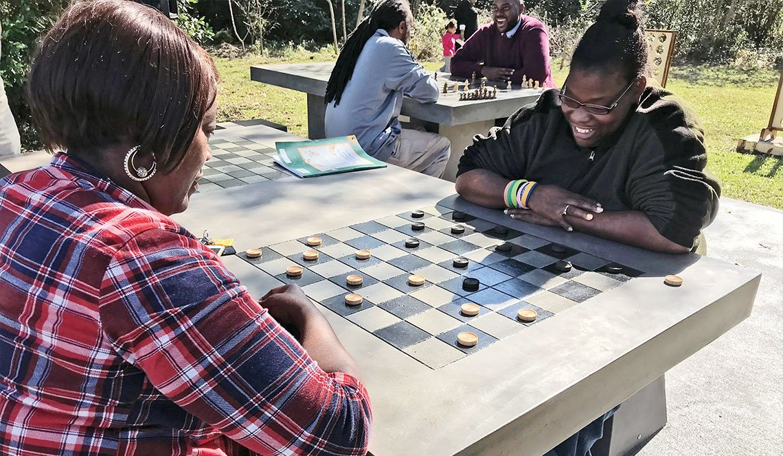 Two young women play checkers at an outdoor game table in Macon, Georgia