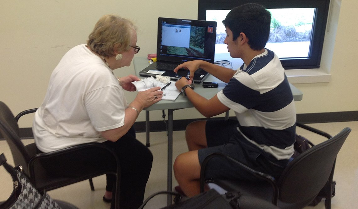 A teenage boy teaches an older woman how to use her digital camera