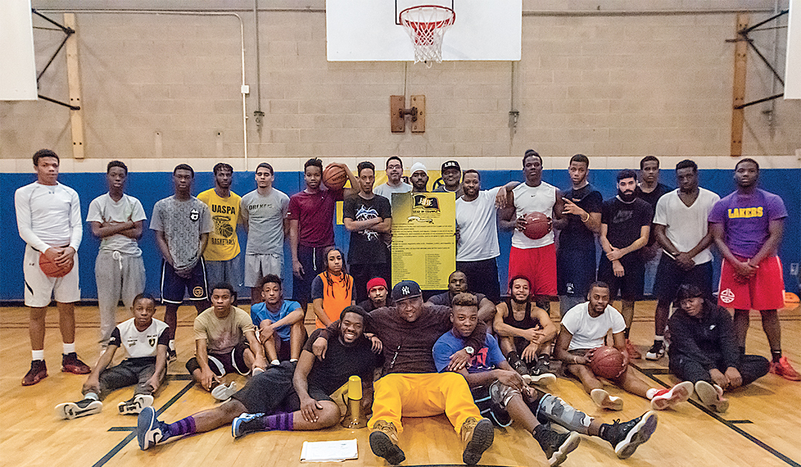 Antonio Hendrickson (seated, wearing yellow pants) poses for a basketball court group photo with young men attending a Lead by Example workshop