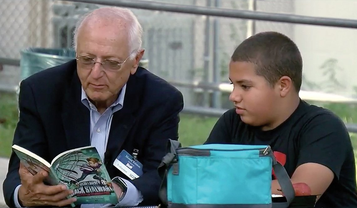 "Volunteer Ron Diner reading a book with Davion, his young ""lunch pal"""