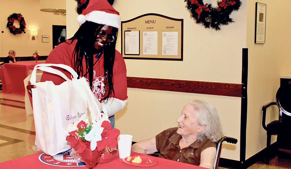 A Silver Stars volunteer delivers holiday gifts to a woman in a nursing home