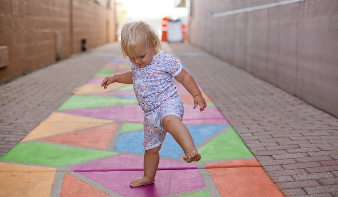 Toddler plays in revitalized alley in Oconomowoc, Wisconsin