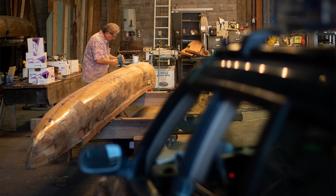 A member of a men's shed works on building a canoe