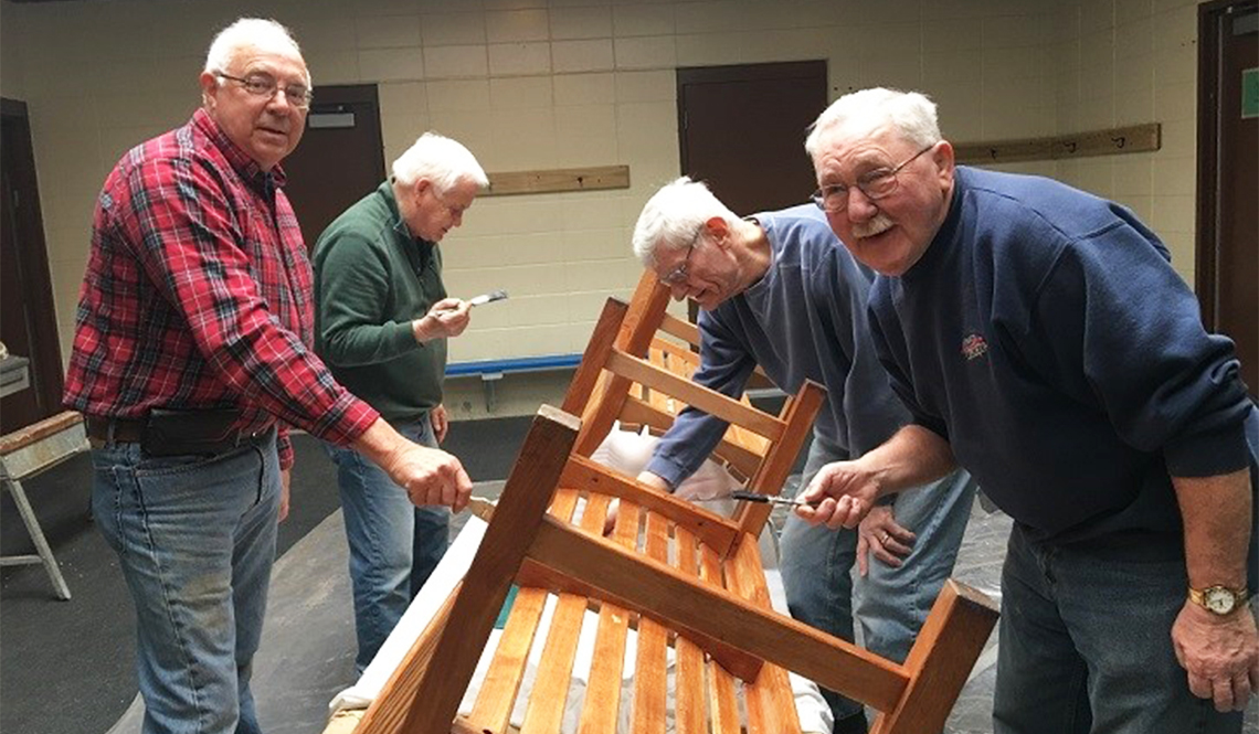 Four men building and staining benches
