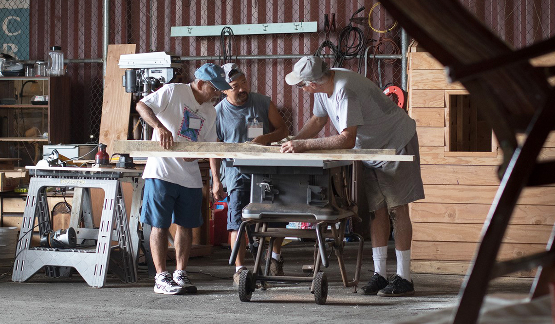 Three men working in a men's shed