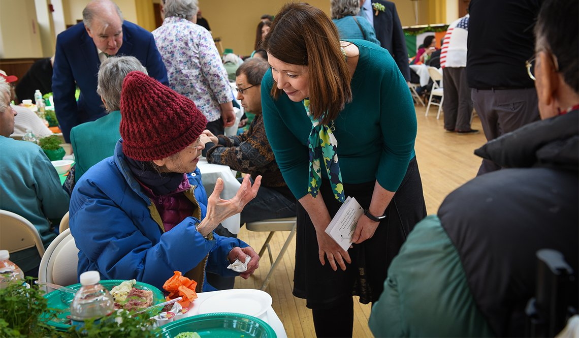 Emily Shea listens to a senior citizen at an event in Boston