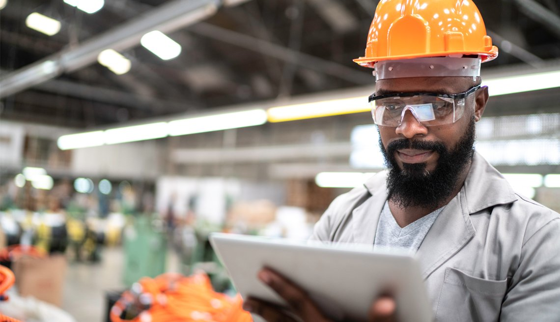 a man in a factory wearing a hard hat using a digital tablet
