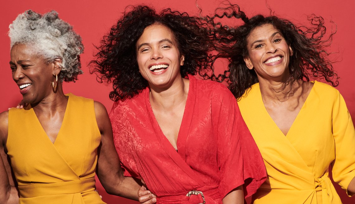a group of three women smiling and laughing