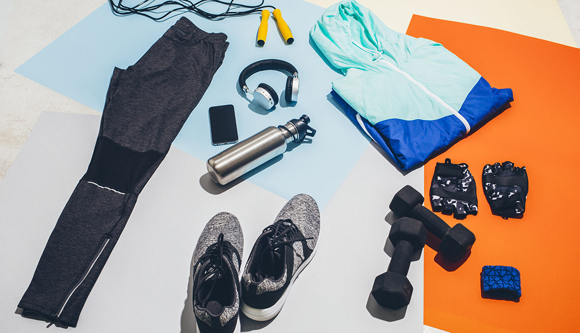 workout outfit and accessories such as hang weights headphones and water bottle are spread out on the floor atop yoga mats