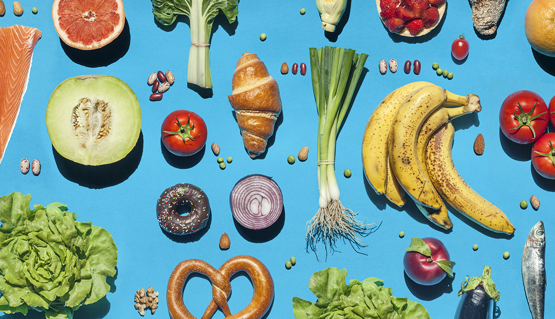 blue background table filled with various foods and featuring colorful fruits and vegetables as the highlights