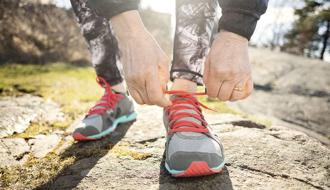 an older persons hands shown as they bend down to tie their sneaker while exercising outside