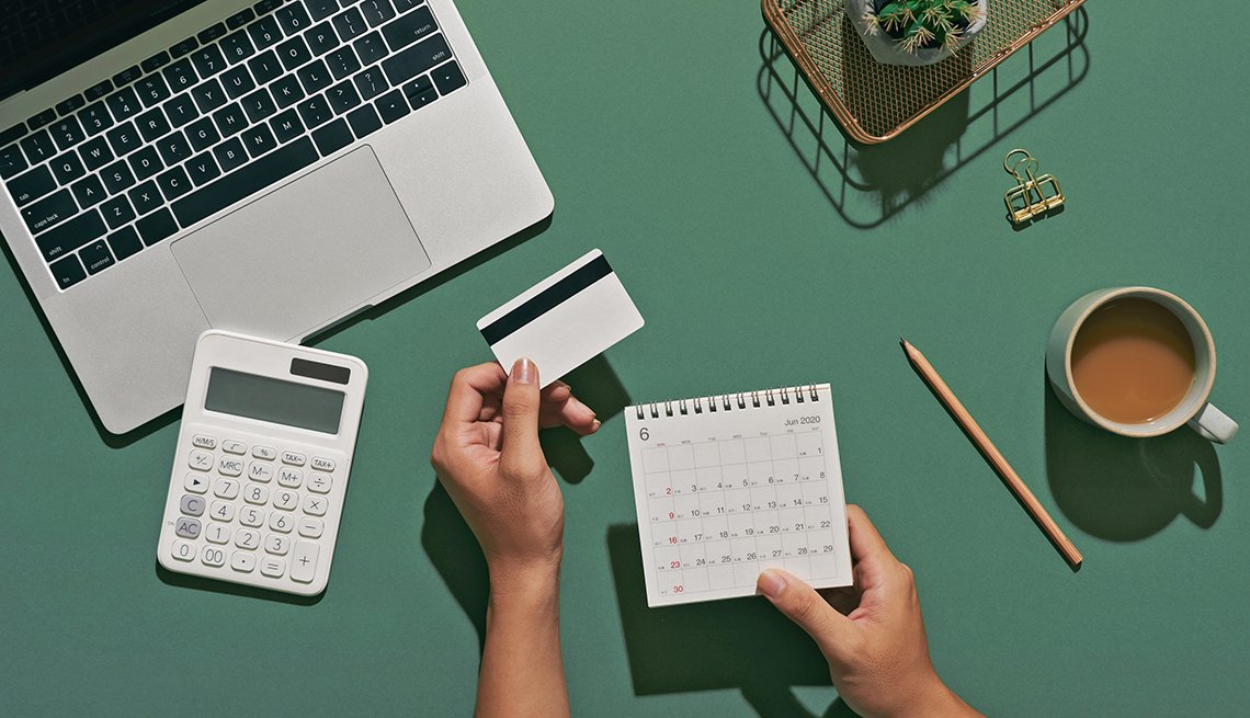 person holding a calendar and credit card at their desktop with a calculator and laptop in front of them