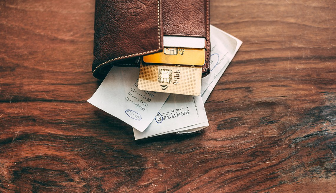a leather wallet on a table with credit cards and receipts hanging out of it