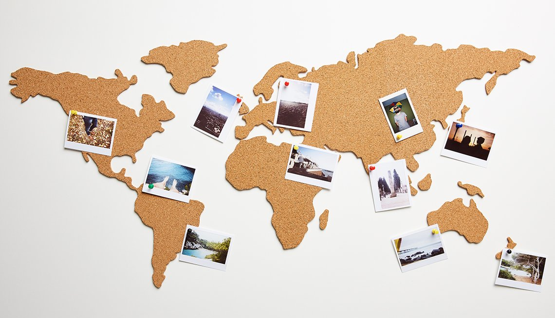 world map made of cork board with push pins on polaroid shots of different locations