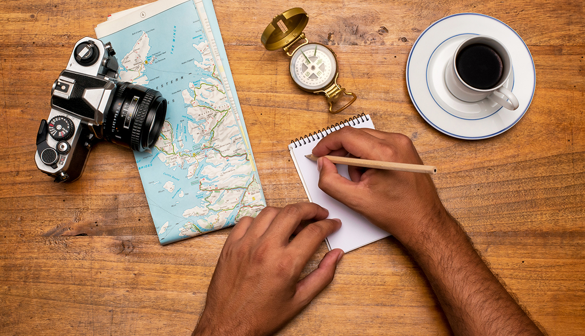 view of desk from above showing a mans hands as he takes notes while planning a trip surrounded by a camera a map and a cup of coffee