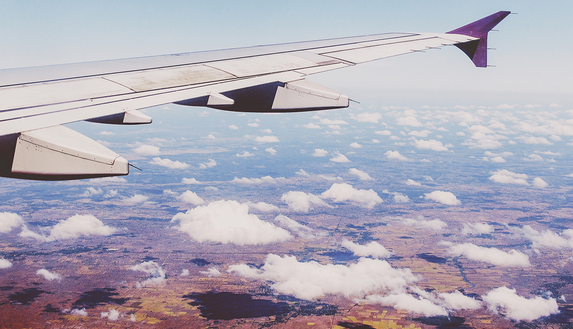 view of an airplane wing and the clouds and ground below taken from one of the plane windows while in flight