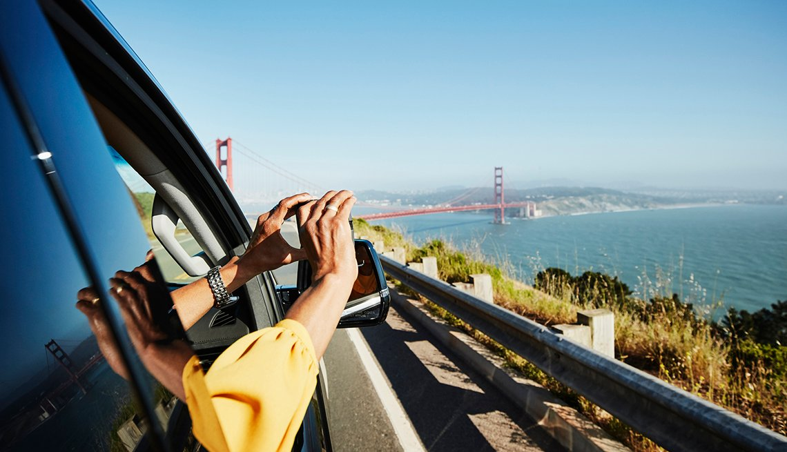 woman in car holding phone out the open window taking a photo of the golden gate bridge over the san francisco bay