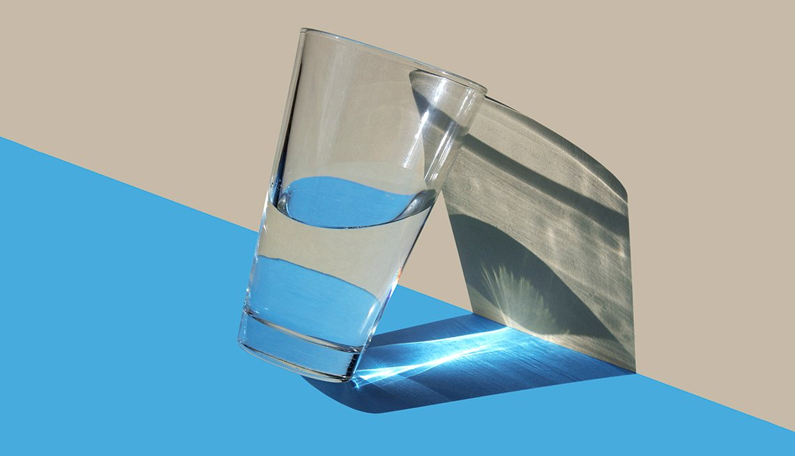 half glass of water against a wall