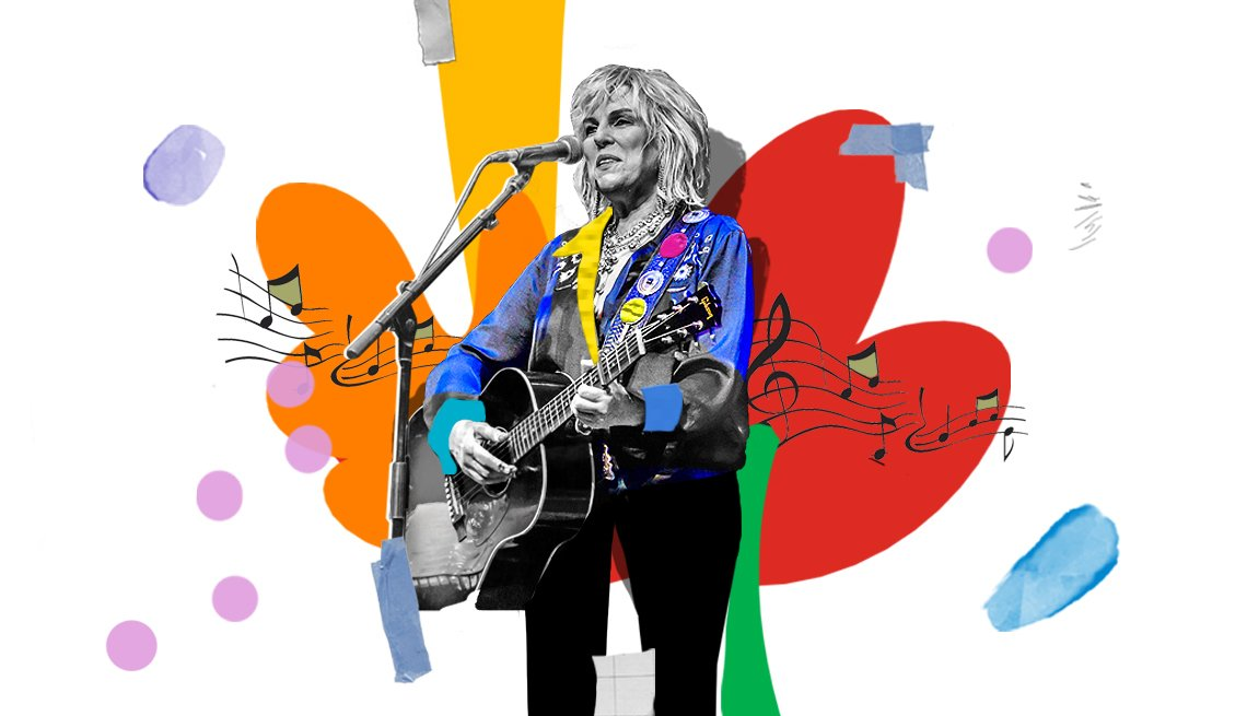 lucinda williams holding a guitar in front of microphone
