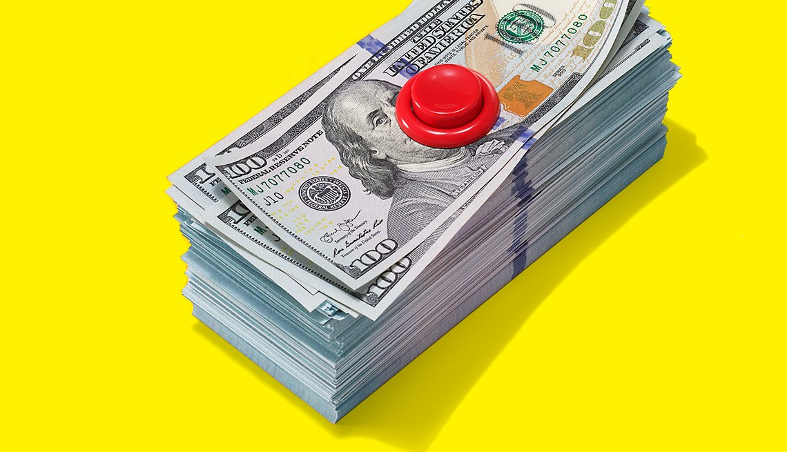 A pile of money with a red button on top