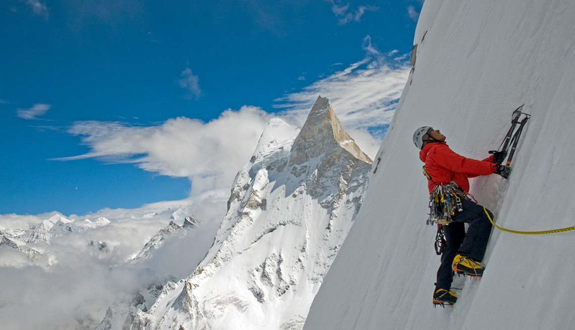 Climber Jimmy Chin ascending snowy face of Meru under blue sky, white clouds, and snowy peaks