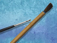 Thin and thick paintbrushes on blue background