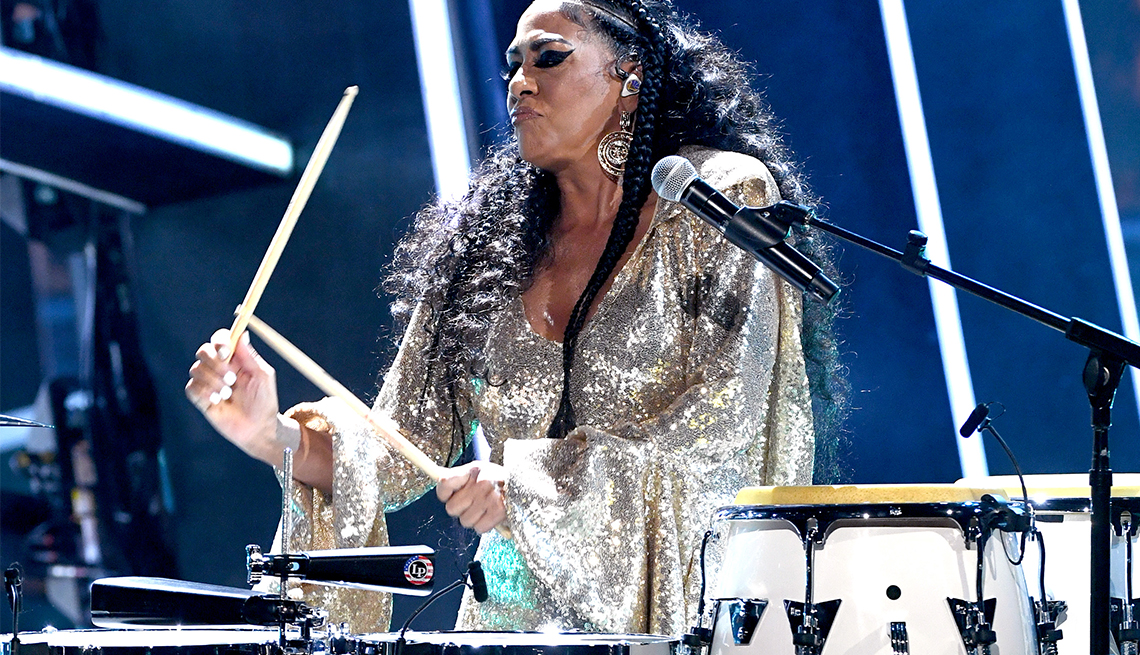 sheila e playing drums and wearing sparkly silver outfit