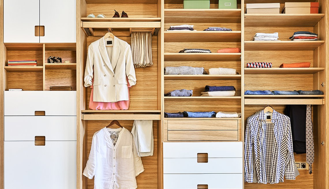 very organized wood and white closet with clothes neatly folded on shelves and hanging