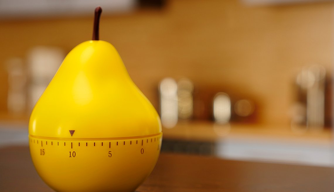 timer in the shape of a yellow pear set to 10 minutes on a kitchen counter