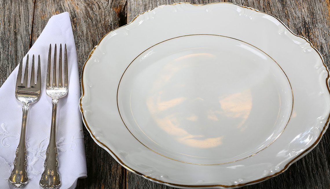 fine china dinner plate and silverware on fancy white napkin