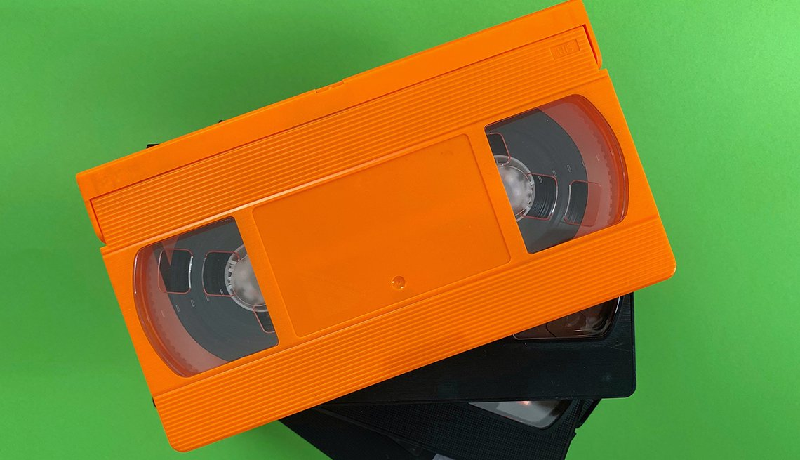 one orange and two black VHS tapes on green background