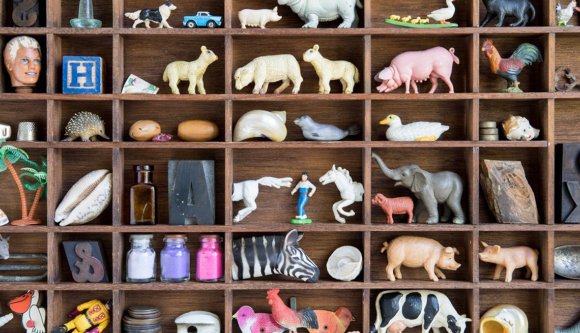 little animal figures and other collectibles organized in wooden box frame