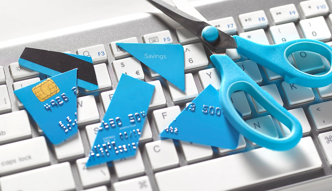 blue scissors and cut up credit card on computer keyboard