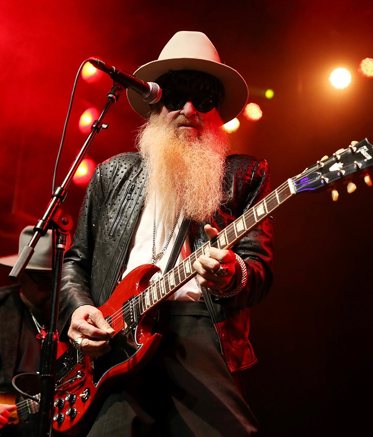 Billy F. Gibbons of ZZ Top performing onstage with red guitar