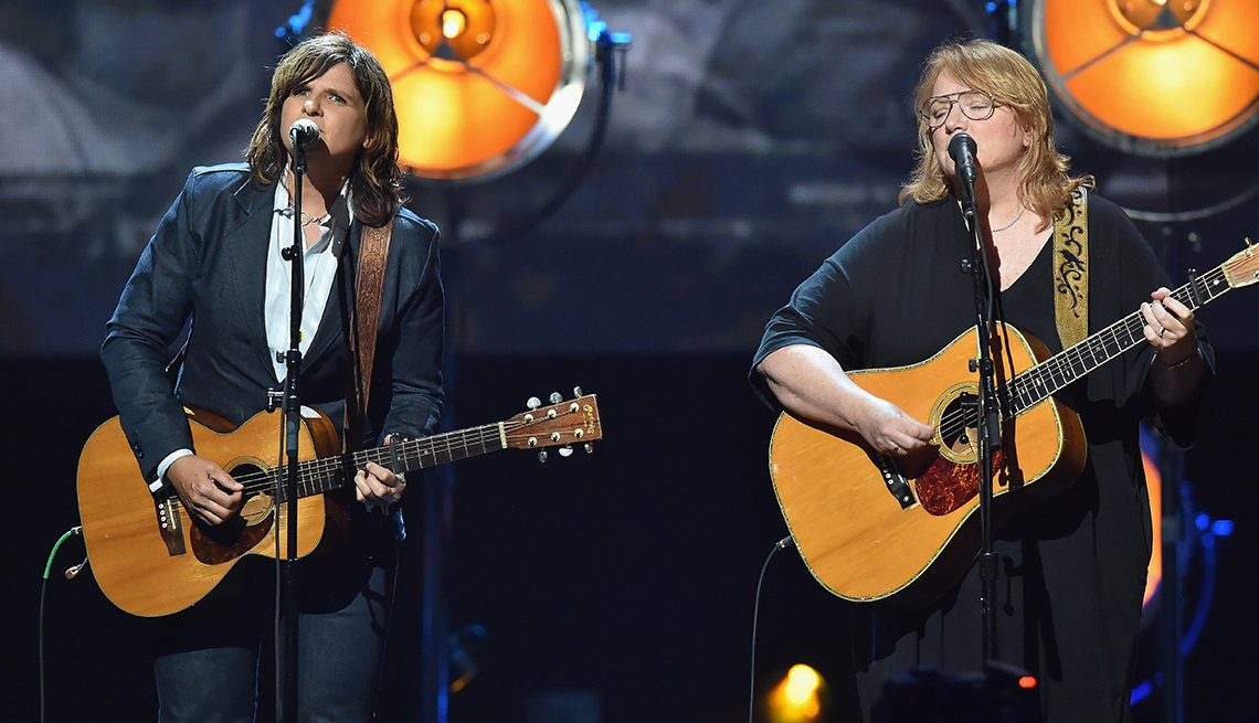 Indigo Girls onstage singing and playing guitar