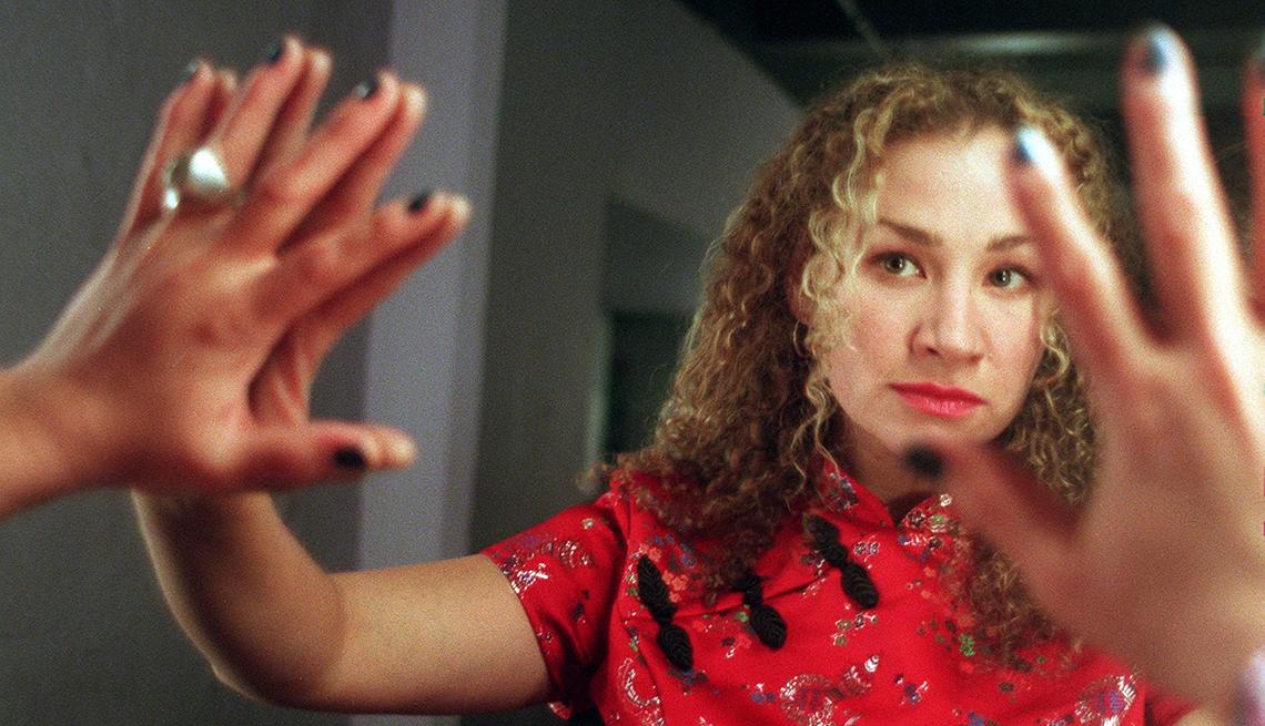 Singer Joan Osborne in red dress reflected in mirror