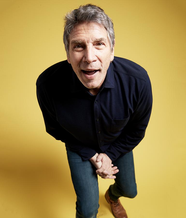 current photo of former MTV vj Mark Goodman on yellow background