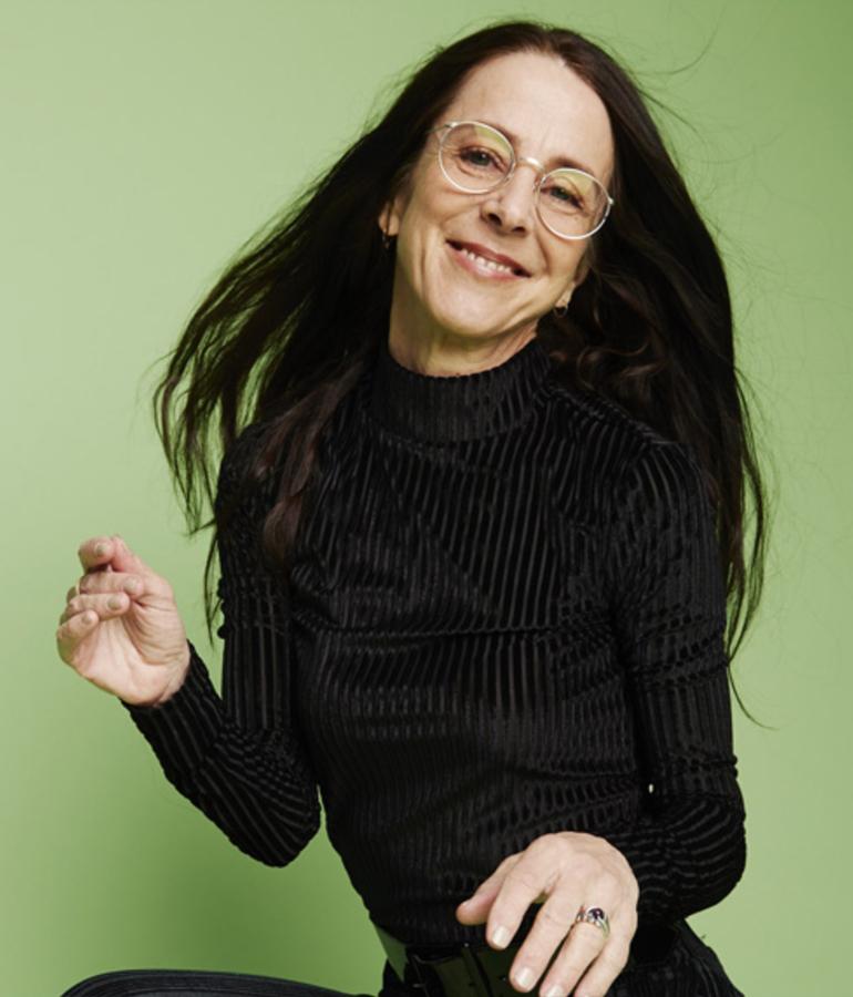 current photo of former MTV vj Martha Quinn on green background