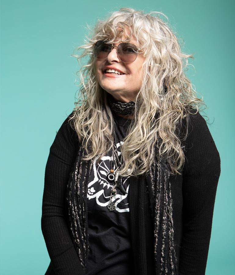 current photo of former MTV vj Nina Blackwood on teal background