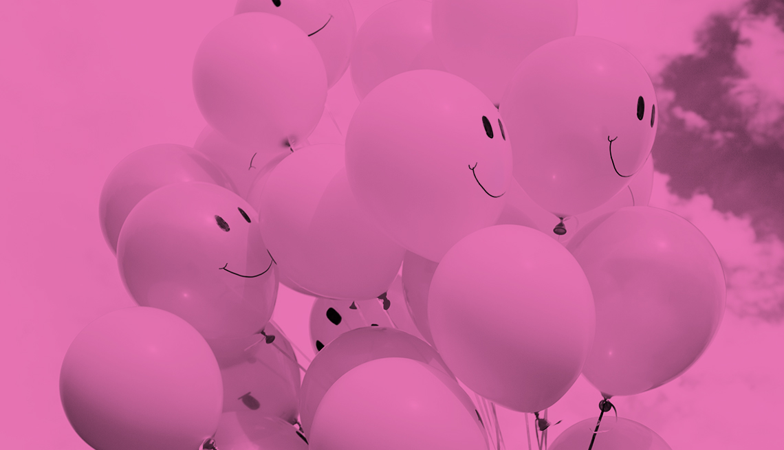 bunch of pink balloons with smiley faces against a pink background